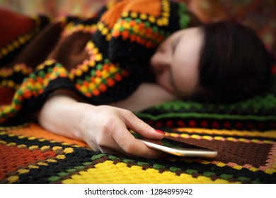 Loneliness and longing. A woman is sleeping while holding a phone in her hand.