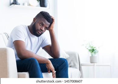 Loneliness. Stressed african american guy thinking about problems at home alone, free space