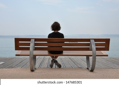 Loneliness teenager sitting on a bench at the sea shore