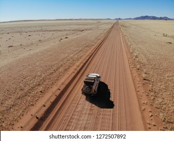 Lonely 4x4 car driving through vast Namib Naukluft National Park, Namibia
