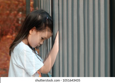 Lonely 5 years old Asian girl stand leaning against a steel fence.Concept of lonely child or kid in trouble or kid violence.