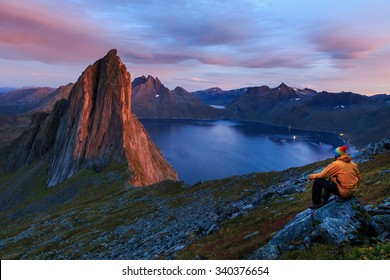 Lonely adventurer is amazed by the breathtaking view on rugged peak of Segla mountain on Senja island, Norway