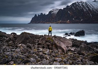 Lonely adventurer is amazed by the breathtaking view on rugged peak of mountain on Senja island, Norway