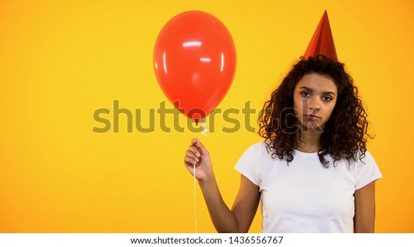 Lonely african woman holding red balloon, feeling sad on birthday celebration