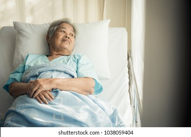 lonely asian elderly female patient lying on the bed in the hospital and looking away outside the window waiting to see her child and her family to visit.