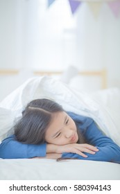 Lonely Asian girl lying on the bed