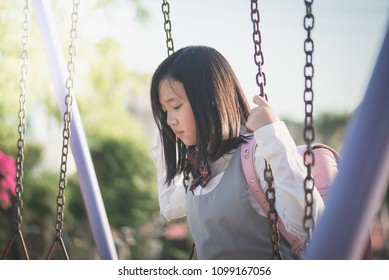 Lonely Asian girl sitting on chain swing in the park