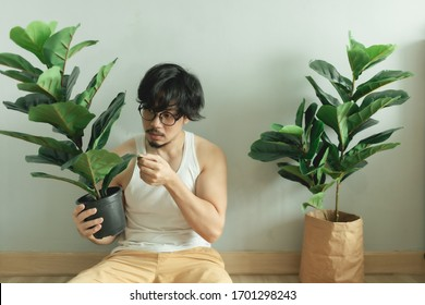 Lonely Asian man being friend with his tree plant in the apartment.