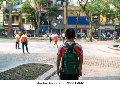 Lonely Asian school boy watches his friends play football outdoor in city