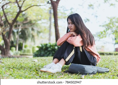 Lonely asian woman sit alone in the park,Sad thai woman think something,Heartbreak girl concept