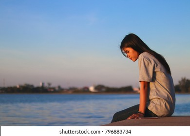 Lonely asian woman sit alone in the park,Sad thai woman think something,Heartbreak girl concept, soft focus.