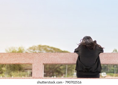 Lonely asian woman sitting back alone in the park,Sad thai woman think something,Heartbreak girl concept