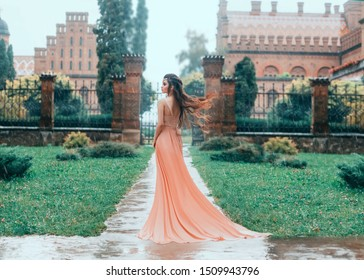 Lonely Attractive brunette woman walks in the rain near the stator castle. Young princess in a pink wet dress with a train. Hair fluttering, flying in the wind. Autumn sad landscape.
