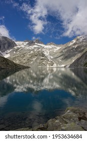 Lonely and austere Lake Vedretta at an altitude of 2600 meters. View of the high altitude lake framed by the mountains reflecting in the water. Adamello Brenta Natural Park, Italy. Vertical immage.