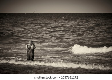 Lonely bass fisherman on the coast