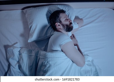 A lonely bearded dark-haired man sleeps soundly on his left side at night in bed. Close-up from above, orthopedic pillow, bedroom, self-isolation. One