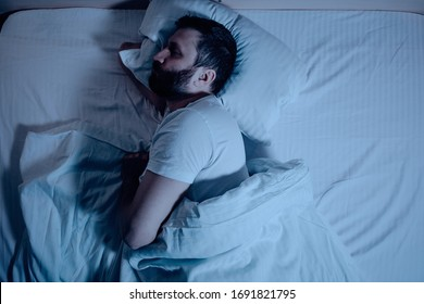 A lonely bearded dark-haired man sleeps soundly on his stomach at night on the bed. General plan from above, orthopedic pillow, bedroom, self-isolation. One