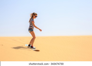 Lonely beautiful girl doing sand boarding in a desert