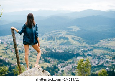 Lonely beautiful long haired young traveler girl with sexy legs in jeans clothes standing on stone at top of carpathian mountain with wooden staff stick and looking at village far at horizon.