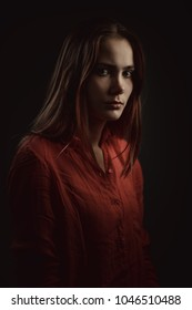 Lonely beautiful woman in coral shirt attentively looking at camera on dark background, low key studio shot
