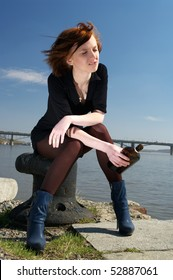 Lonely beautiful young woman sitting on pier with a whiskey bottle, feeling very sad.