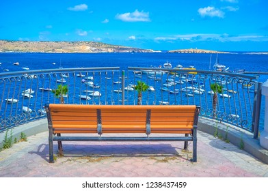 The lonely bench on the hill with a great view on coastline and harbor of Bugibba resort, Malta
