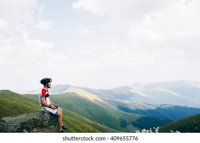 Lonely biker man bicyclist sit at mountains and dream