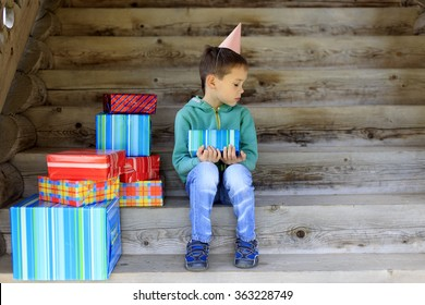 lonely birthday. one of the favorite and dear people did not come to the birthday to the little boy. child sits alone surrounded by gifts and sad looking an empty place next to him.