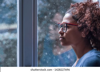 Lonely black woman near window thinking about something and winter snow