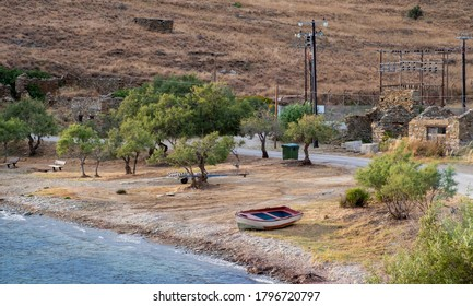 Lonely boat and benches at Kokka beach, Kea, Tzia Greek island, tourism destination Greece. Summer holidays next to sandy calm sea, Ruined buildings, nature background.