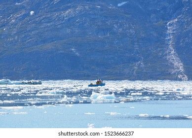 lonely boat between icebergs in the arctic sea -  Eqip Sermia - Eqi Glacier in Greenland Disko Bay - World heritage -  extremly affected by global warming and climate change. Summer, July