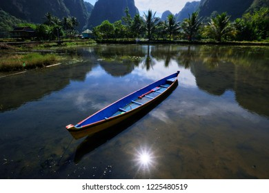 lonely boat on the mid day, we can see the karst reflected on the water. This place is Rammang-rammang, the 3rd biggest Karst in the world