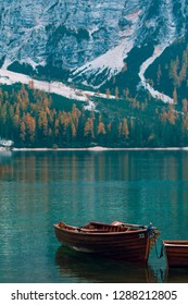 Lonely boat on the mountain lake in front of autumn yellow forest and rocks. Lago di Braies, Italy. Peaceful landscape