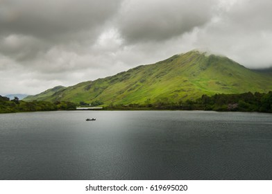 A lonely boat sails across the smooth waters of Pollacapall Lough in Connemara, County Galway, Ireland.
