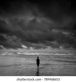 lonely boy  alone looking at the horizon near the beach during storm, black and white photography.