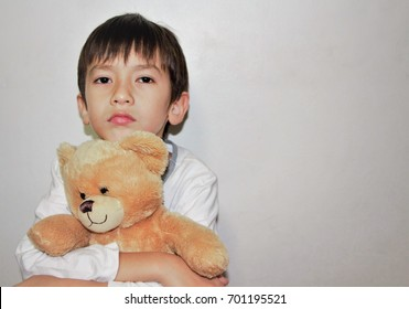 A lonely boy cuddles his teddy bear stays at home alone without parents.