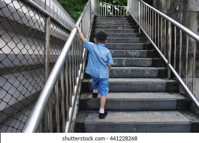 lonely boy  walking on stairs outdoors/ Asian baby/ thai student .