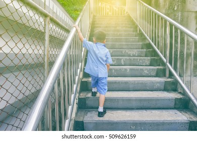 lonely boy walking on stairs outdoors/ Asian baby/ thai student
