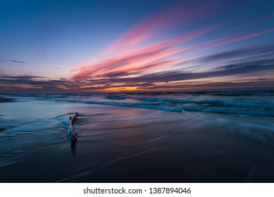 lonely branch covered with gentle waves and a beautiful sunset on a clean, empty, sandy beach on the Polish sea