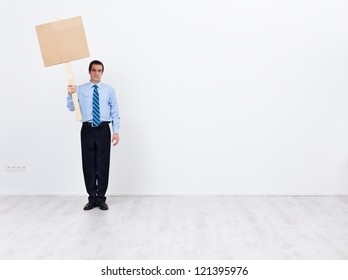 Lonely businessman with blank sign placard and lots of copy space