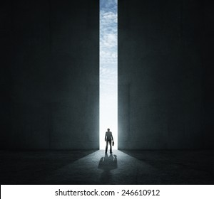 Lonely businessman standing in front of the huge gate