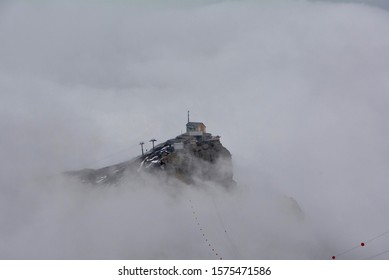 The lonely cable station on the top of the mountain near Schilthorn summit, Switzerland, in the misty day.