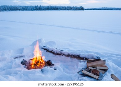 Lonely campfire burning in cold winter evening
