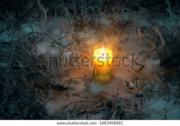Lonely candle in the winter on the ice at night. Christmas festive burning candle standing on icy snow surrounded by icy grass. Candle is a symbol of divine light, grace and faith, spiritual joy.