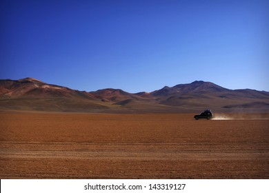 Lonely car going trough Salvador Dali Desert in Altiplano, Bolivia