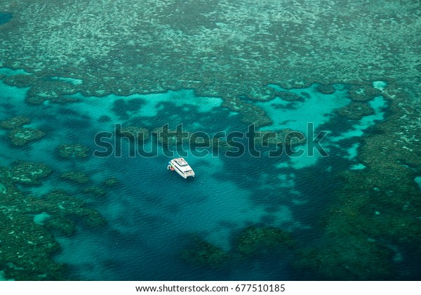 Lonely catamaran in the Great Barrier Reef as seen on the outer reef away from the Whitsunday Islands and Airlie Beach.