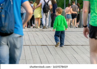 Lonely Caucasian little boy get lost in crowd and looking for his parents back view