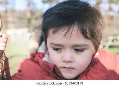 Lonely child with a sad face sitting alone on swing in the playground in retro filter, Poor kid boy with upset face playing alone at outdoors play area, Spoiled child, lost children concept