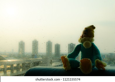 lonely clown sit near the window with cityscape background in high contrast concept