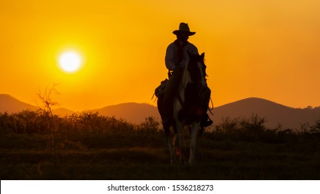 A lonely Cowboy riding horse  at sunset.